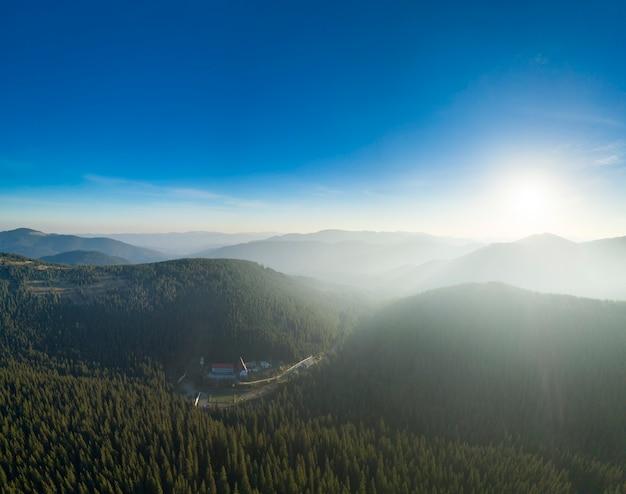 Splendida alba in montagna, i raggi del sole illuminano le cime delle montagne attraverso la nebbia.