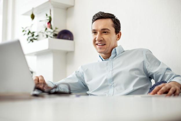 Splendida giornata. bell'uomo dai capelli scuri ordinato esuberante che sorride e lavora al suo laptop mentre era seduto al tavolo