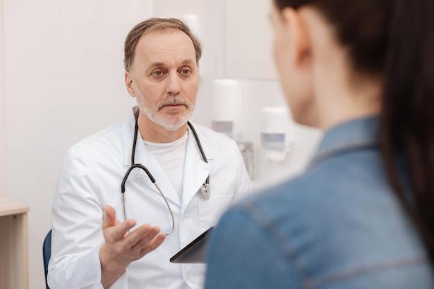 Meraviglioso cardiologo esperto e amichevole che ha una conversazione aperta con la giovane donna sulla sua diagnosi mentre cercava di capire i modi per curare quella malattia