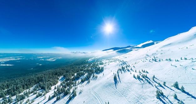 Meravigliosi cumuli di neve giganti sulle colline nelle montagne coperte di neve in una soleggiata giornata invernale gelida