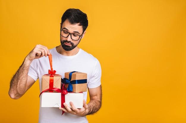 Regali meravigliosi! foto adorabile dell'uomo barbuto attraente con bel sorriso che tiene scatole regalo di compleanno isolate su sfondo giallo.