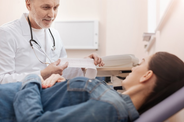 Meraviglioso specialista di spicco bello che dimostra un cardiogramma e spiega cosa significa per la giovane donna