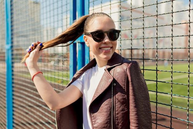 Meravigliosa ragazza felice in occhiali da sole con acconciatura scura cammina per strada di buon umore in una giornata calda e soleggiata