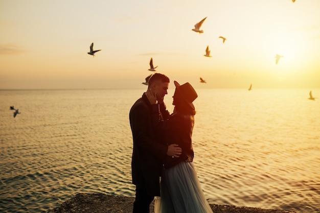 Meraviglioso paesaggio con giovane coppia di turisti al tramonto dorato e gabbiani in volo sulla spiaggia.