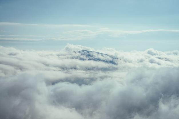 Meraviglioso paesaggio minimalista con cima di montagna sopra dense nuvole basse. il vertice della montagna galleggia in nuvole spesse. minimalismo scenico con picco di montagna sopra il cielo nuvoloso. bella vetta nella nuvolosità.