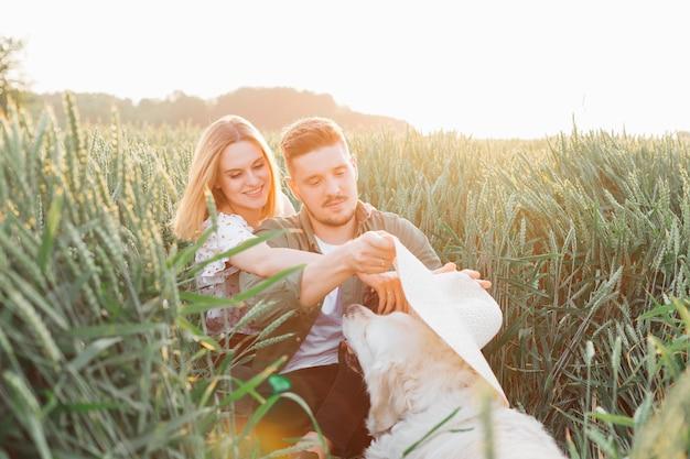 Momenti meravigliosi di comunicazione tra giovane coppia e golden retriever. amore e tenerezza. bei momenti di vita. pace e disattenzione. camminare nella natura. stile di vita.