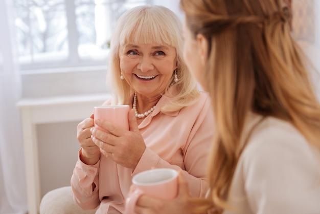 Stato d'animo meraviglioso. donna invecchiata felice felice che sorride e che guarda sua figlia mentre prende il tè con lei