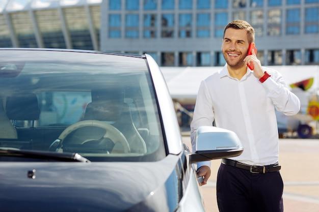 Stato d'animo meraviglioso. uomo positivo allegro che tiene la sua portiera della macchina mentre la apre