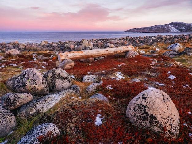 Meraviglioso paesaggio di montagna con tundra e una panchina sulla riva del mare di barents. teriberka.