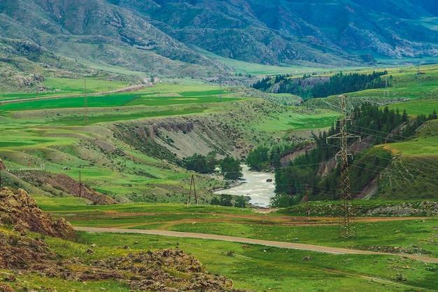 Montagne meravigliose con copertura forestale e fiume di montagna. linee elettriche negli altopiani.