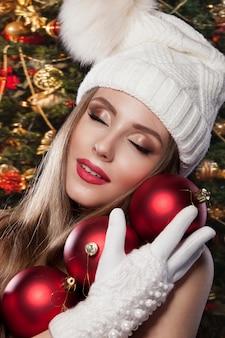 Una meravigliosa foto di capodanno. una bella ragazza con un cappello e guanti è in possesso di palline rosse