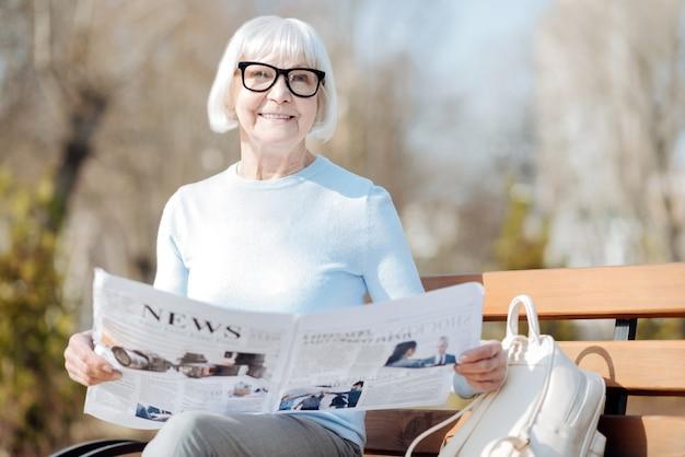 Notizie fantastiche. avvisare la donna invecchiata leggendo un giornale mentre è seduto sulla panchina