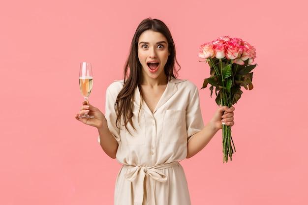 Concetto meraviglioso di notizie, celebrazione ed emozioni. allegra attraente donna bruna in abito, mani aperte lateralmente sorpreso e meravigliato, bocca aperta ansimante, tenere il bicchiere di champagne e fiori
