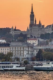 Meraviglioso paesaggio urbano al tramonto con la chiesa di mattia su uno sfondo di alba illuminato cielo arancione a budapest, ungheria.
