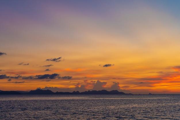 Meraviglioso paesaggio al tramonto in riva al mare, i colori del cielo al tramonto e la silhouette dell'isola nell'acqua incredibile tramonto tropicale.