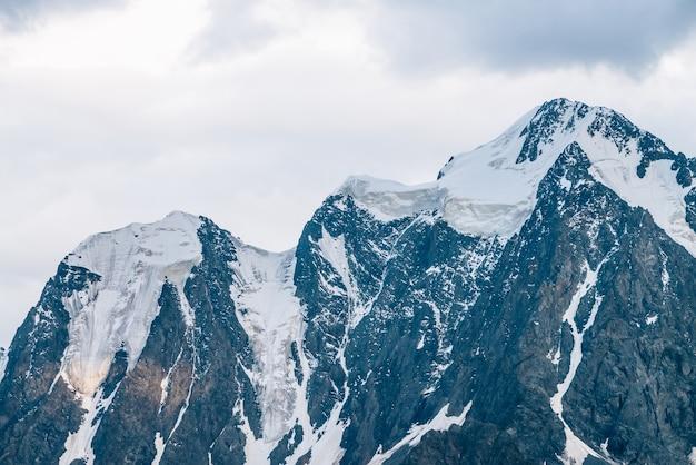 Primo piano meraviglioso del ghiacciaio del sole. raggio di sole sulla cima della montagna innevata. cresta rocciosa con neve nella mattina di sole. incredibile catena montuosa con luce solare. atmosferico paesaggio minimalista di natura maestosa.