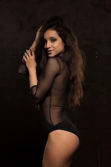 Meravigliosa giovane donna abbronzata con corpo atletico in lingerie trasparente in posa nell'ombra
