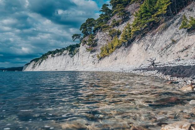 Una splendida vista dalla superficie dell'acqua alla costa del mar nero. alberi verdi su rocce bianche e cielo nuvoloso blu drammatico. blue deep - golubaja bezdna gelendzhik distretto, regione di krasnodar, russia