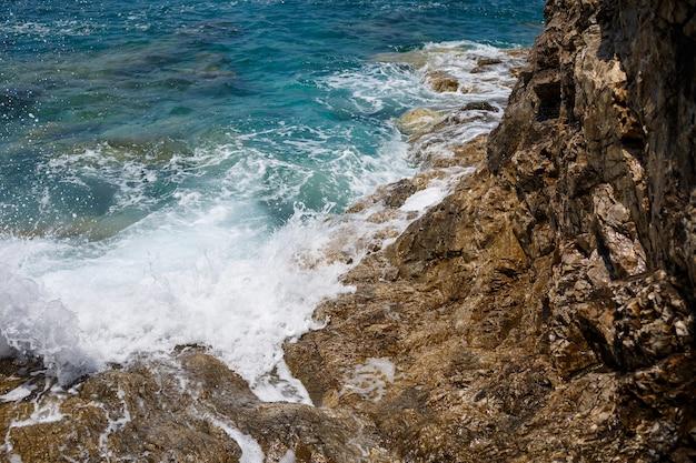 Splendide viste sull'azzurro mar mediterraneo. rocce soleggiate, onde con schiuma e spruzzi d'acqua. l'onda si infrange sugli scogli sulla riva