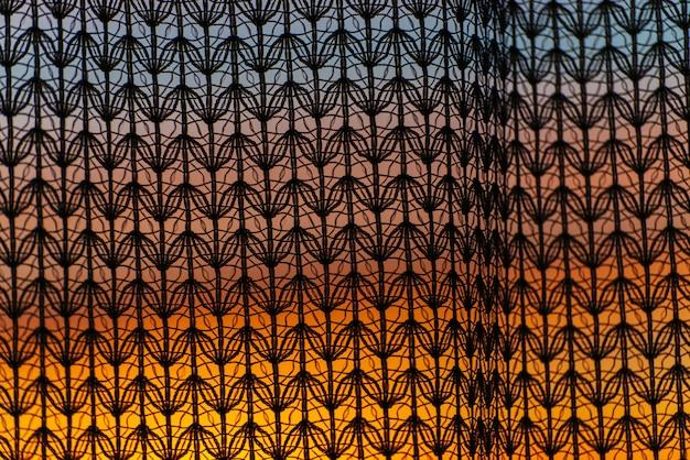 Splendida alba vivida dalla finestra attraverso la tenda a motivi geometrici. incredibile cielo caldo dietro le sagome della trama di tulle. luce solare arancione.