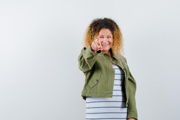 Donna meravigliosa che indica con il dito in giacca verde, camicia e gioiosa, vista frontale.