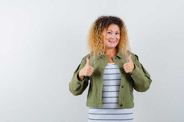 Donna meravigliosa che mostra i pollici in su in giacca verde, camicia e sembra felice, vista frontale.