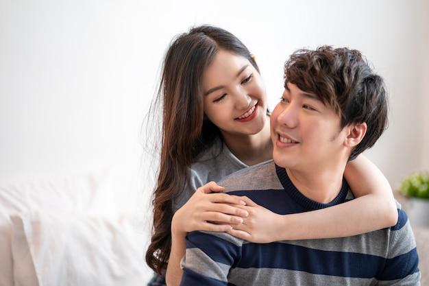 Le giovani coppie asiatiche meravigliose sul letto nell'abbraccio della camera da letto e godono insieme della vita e delle coppie tenere sorridenti che abbracciano a letto la mattina con felicità