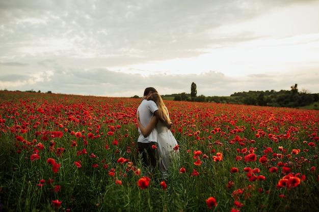 Le giovani coppie meravigliose abbracciano e si godono la vita insieme allo stile di vita naturale di attività per il tempo libero all'aperto al campo di papaveri scarlatti durante l'estate