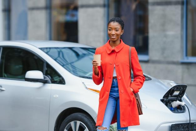 Chiedendosi della nuova tecnologia. donna sulla stazione di ricarica per auto elettriche durante il giorno.
