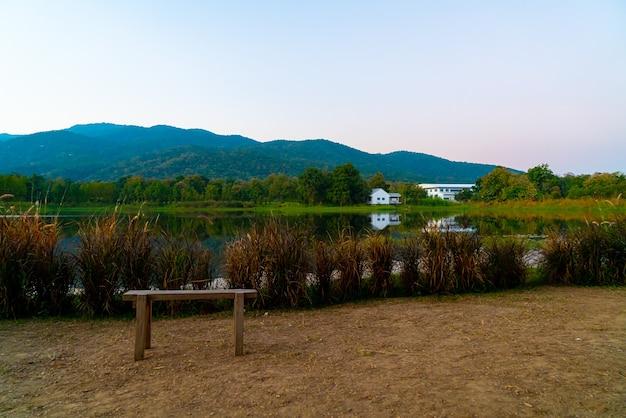Panca in legno con bellissimo lago a chiang mai con montagne boscose e cielo al crepuscolo in thailandia. Foto Premium