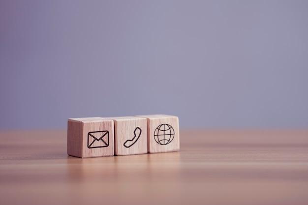 Blocco di legno cubo simbolo mail telefono sociale su tavola di legno