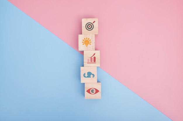 Blocco di legno con strategia aziendale icona e piano d'azione. obiettivo e obiettivo, successo e concetto di obiettivo aziendale, gestione del progetto, sviluppo della strategia aziendale. copia spazio.