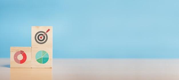 Blocco di legno con strategia aziendale icona e analisi dei dati finanziari del grafico commerciale forex. obiettivo e obiettivo, successo e concetto di obiettivo aziendale, sviluppo della strategia aziendale. copia spazio.