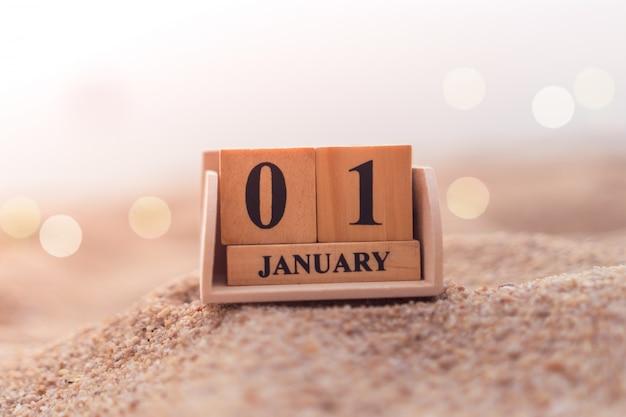 Calendario di data e mese di manifestazione del blocchetto del mattone di legno. 1 ° gennaio o capodanno concetto.