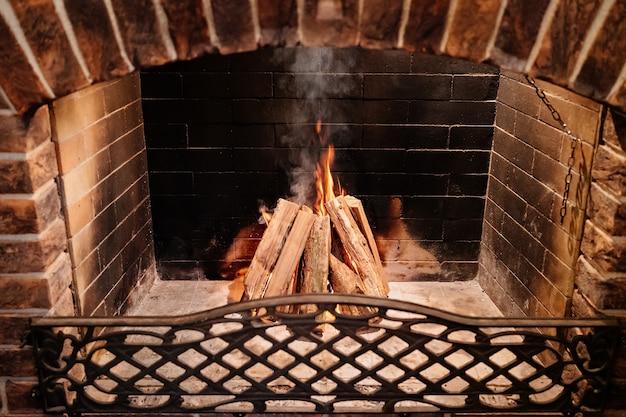 Brucia la legna nel camino. calde serate accoglienti in una casa di campagna. stile retrò. camino in pietra all'interno. luce bassa. profondità di campo ridotta.