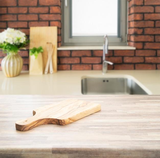 Piano di lavoro in legno sulla sfocatura dello sfondo della stanza della cucina. per la visualizzazione del prodotto di montaggio o il layout visivo chiave.