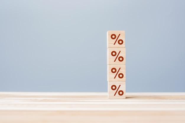 Blocco cubo di legno con icona simbolo di percentuale. tasso di interesse, concetto finanziario, di classifica e di tassi ipotecari
