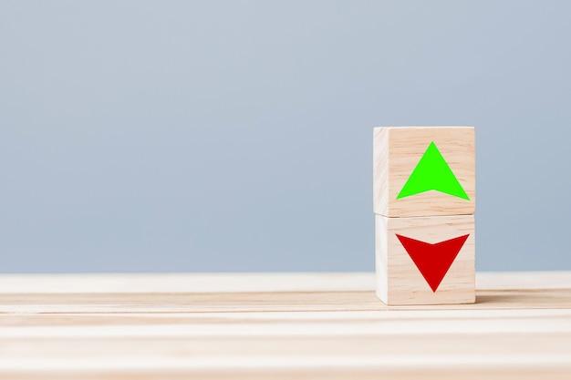 Blocco cubo di legno con icona simbolo freccia su e giù sul tavolo. tasso di interesse, azioni, finanziaria, classifica, tassi ipotecari e concetto di perdita di taglio