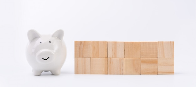 Cubi di legno e salvadanaio isolati su bianco