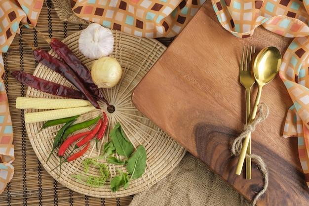 Tagliere di legno con erbe tailandesi e cucchiaio e forchetta con spazio libero per lo sfondo del testo