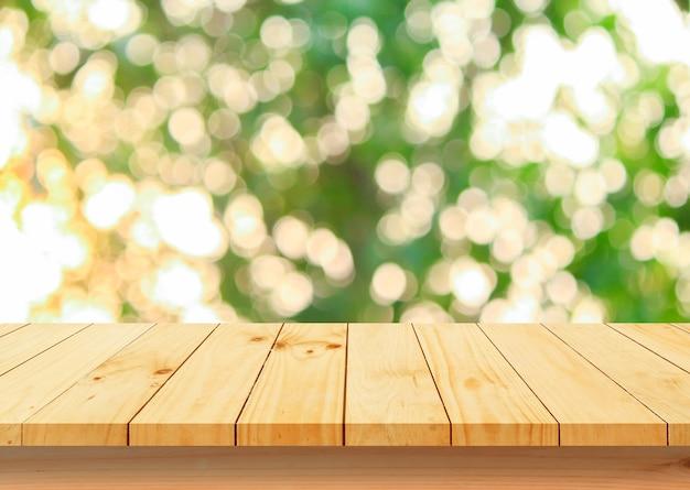 Pavimento in legno con alberi sfocati bokeh di fondo del parco naturale