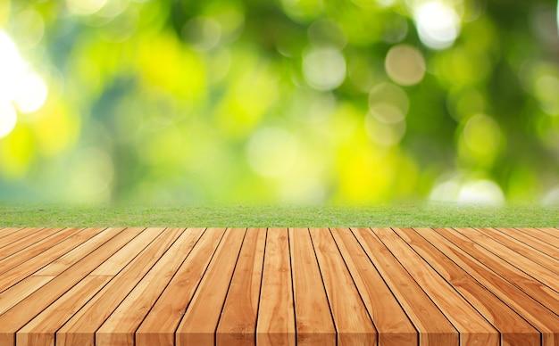 Pavimento in legno con alberi sfocati dello sfondo del parco naturale e della stagione estiva