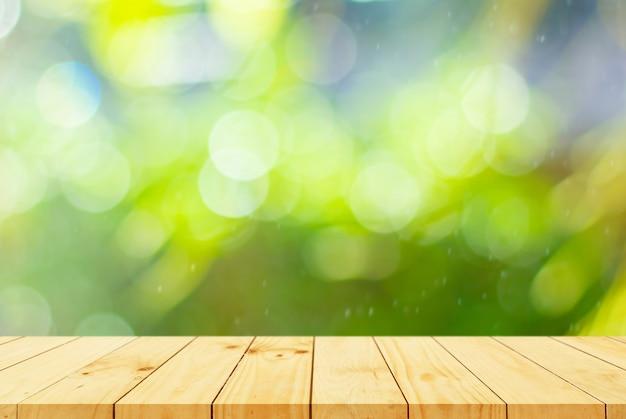 Pavimento in legno con alberi sfocati sullo sfondo del parco naturale