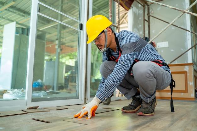Lavoratori della pavimentazione di legno, muratore che installa il nuovo pavimento di legno laminato a casa.