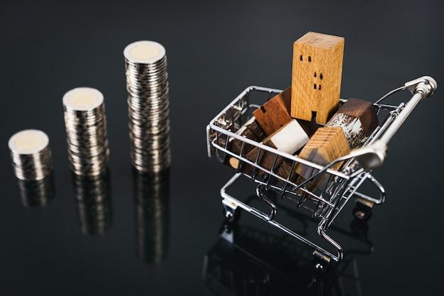 Casa di legno nel carrello sul tavolo scuro con fila di soldi moneta