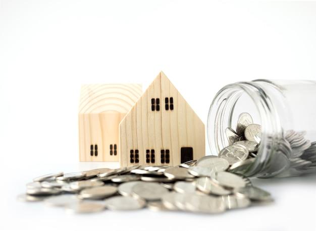 Modello di casa in legno, monete sparse dal barattolo di vetro isolato su bianco