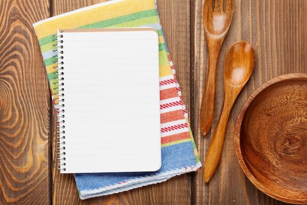 Utensili da cucina in legno su sfondo tavolo in legno con blocco note per spazio copia