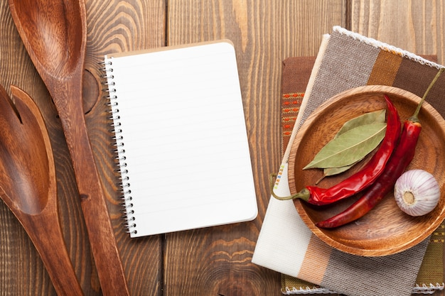 Utensili da cucina in legno su sfondo tavolo in legno con blocco note per spazio copia Foto Premium