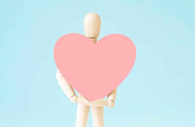 Wood man holding cuore su sfondo di sughero bordo spazio vuoto copia per iscrizione o oggetti. segno idea simbolo, concetto di amore