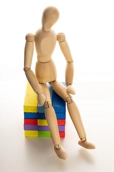 Manichino di legno su sfondo bianco siediti e pensa nello spazio del personaggio